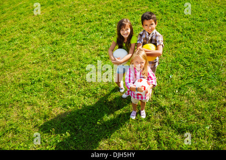 Team of three happy kids, boy and girls standing in the sunny summer park holding sport balls, view from top - Stock Photo
