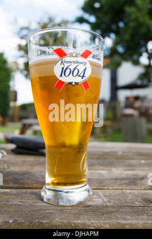 Pint of Kronenbourg 1664 lager on a table in a pub garden - Stock Photo