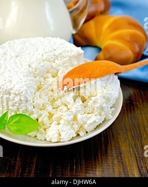 Cottage cheese in a saucer with basil, wooden spoon, two bagels, a pitcher of milk, napkin on wooden board - Stock Photo