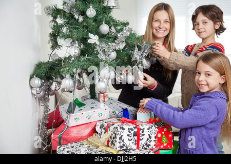 Mother And Siblings Decorating Christmas Tree - Stock Photo