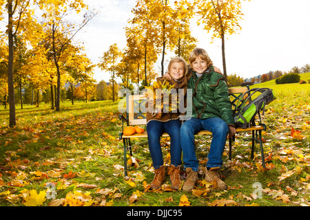 Portrait of two happy blond kids sitting on the bench in autumn park  - Stock Photo