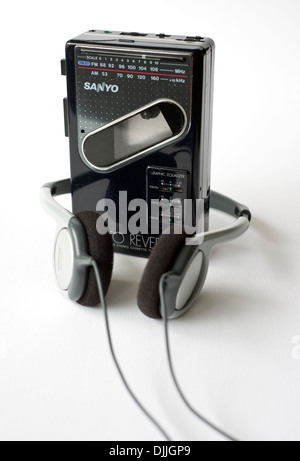 An old Sanyo walkman personal cassette player including radio, along with a pair of headphones, on a white background - Stock Photo