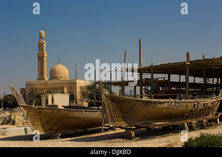 2 Racing Dhows and Mosque with Burj Khalifa in the distance, Jumeirah, Dubai, UAE - Stock Photo