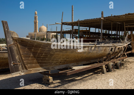 Racing Dhow and Mosque with Burj Khalifa in the distance, Jumeirah, Dubai, UAE - Stock Photo
