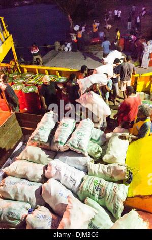 Loadings sacks of copra onto Lady Sandy supply boat, berthed alongside the wharf near Ketei and Tovu. Totoya, Lau - Stock Photo