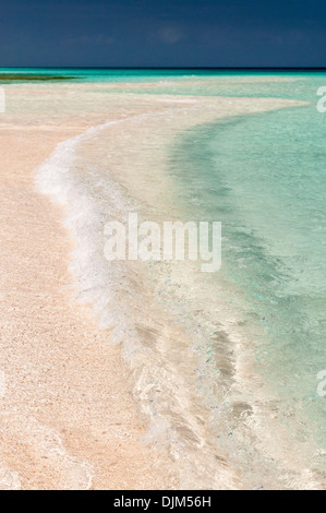 Sunlight on waves breaking on the empty sand spit at the southern end of Huon Island, near low water. Huon Atoll, - Stock Photo