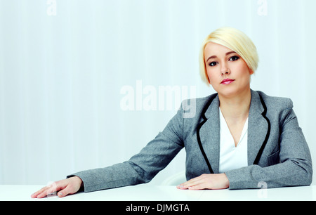 Portrait of a young pensive woman sitting at the table in office - Stock Photo