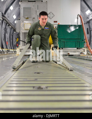 Air Force Reserve Senior Airman Travis Shea, 709th Airlift Squadron loadmaster student, prepares the cargo floor - Stock Photo