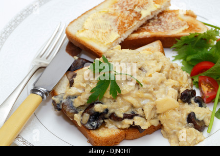 A breakfast or light lunch of scrambled eggs on toast made with fried mushrooms and shallots, - Stock Photo