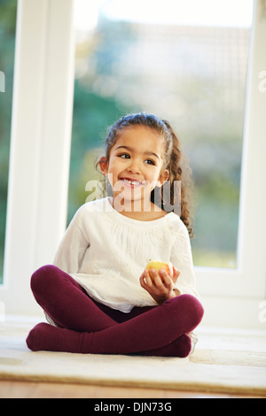 Young girl enjoying eating an apple - Stock Photo
