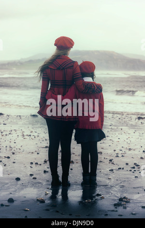 two girls arm in arm at the sea - Stock Photo