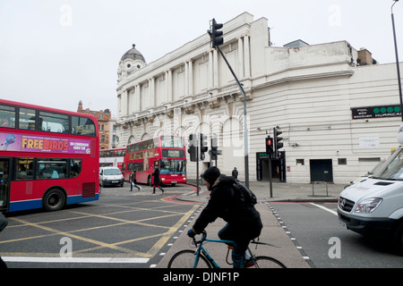 Cyclist riding on bicycle on pedesstrian crossing of busy Grays Inn road in Kings Cross area of London UK  KATHY - Stock Photo