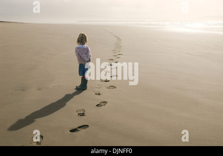 Young girl on a beach looking at footsteps going off into the distance - Stock Photo