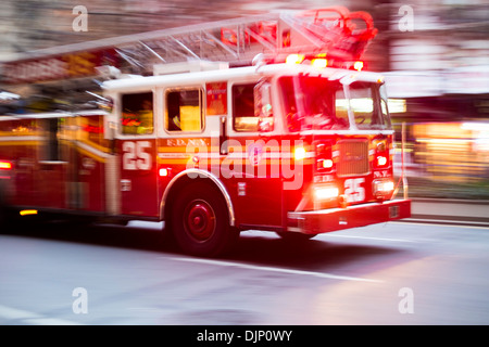 NEW YORK, US - NOVEMBER 21: Motion blurred shot of famous New York fire engine with lights flashing. November 21, - Stock Photo