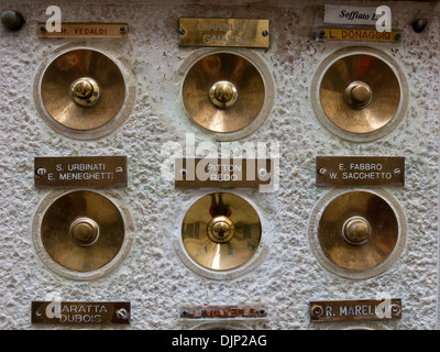 Old ornate decorative brass bell pushes and Italian nameplates, Venice, Italy. - Stock Photo