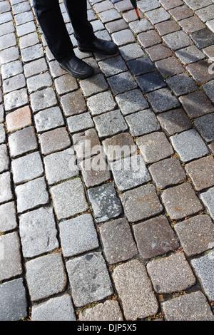 Man, shadow and cobblestones - Stock Photo