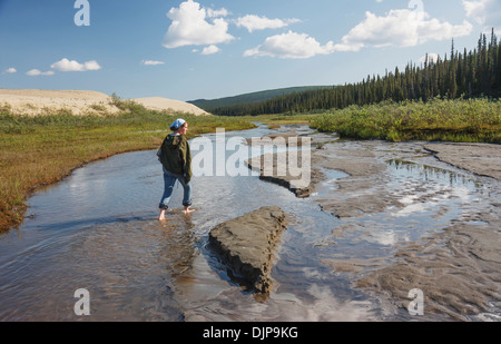 Woman Walks Barefoot In A Creek Along The Edge Of The Great Kobuk Sand Dunes, Kobuk Valley National Park - Stock Photo