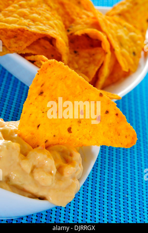 closeup of a bowl with tortilla chips dipped in nacho cheese on a blue background - Stock Photo