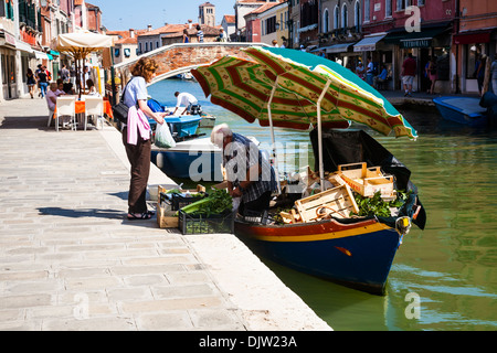 Man selling fruit and vegetables from a boat on a canal, Murano, Venice, Veneto, Italy - Stock Photo