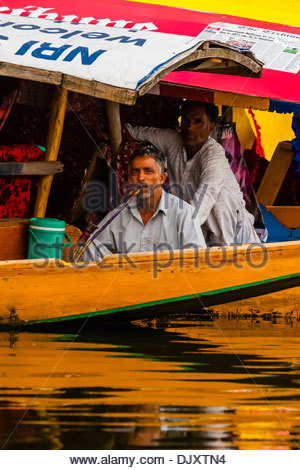 Man smoking a hookah pipe on board a shikara (boat) on Dal Lake in Srinagar, Kashmir, Jammu and Kashmir State, India. - Stock Photo
