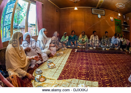 A Muslim engagement party where the bride and grooms families meet, in a houseboat on Dal Lake, Srinagar, Kashmir, - Stock Photo