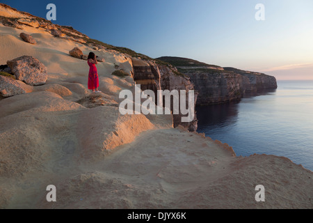 A woman taking pictures of the setting sun from atop the seacliffs at the northwesterly coast of Gozo. - Stock Photo