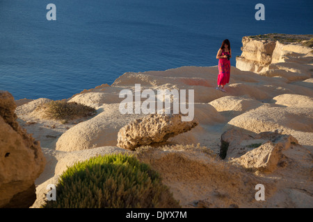 A woman strolling on a plateau eroded into waves by wind erosion in western Gozo seacliffs. - Stock Photo