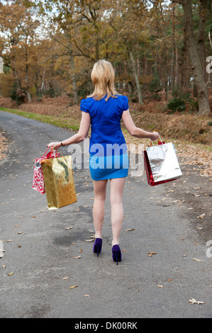 Christmas shopper walking with her packages and carrier bags, her Christmas shopping - Stock Photo