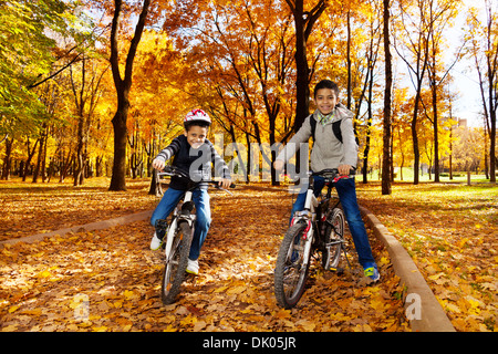 Two black 8 and 10 years old boys ride bicycles, wearing helmet in the autumn maple and oak tree park - Stock Photo