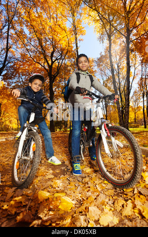 Two cute black smiling 8 and 10 years old boys ride bicycles, wearing helmet in the autumn maple and oak tree park - Stock Photo