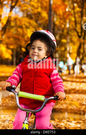 Close portrait of a little black 3 years old black girl riding a bicycle in the park holding stern and wearing helmet - Stock Photo