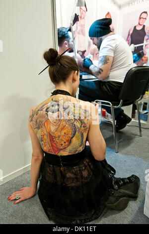 Warsaw, Poland. 1st December 2013. Young tattooed woman sitting in front of tattoo artists and his client during - Stock Photo