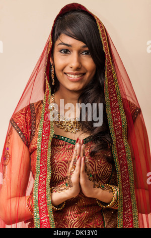 Portrait of a beautiful Indian woman dressed in traditional clothing holding hands in Namaste gesture. - Stock Photo
