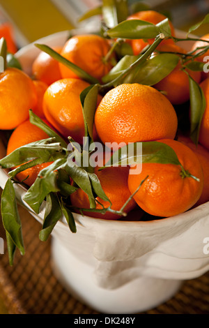 Close up high angle view of ripe orange tangerines in bowl - Stock Photo