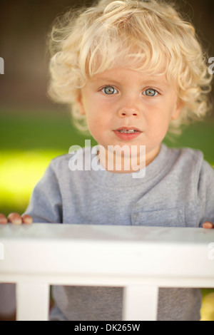 Close up portrait of blonde toddler boy with curls behind fence - Stock Photo