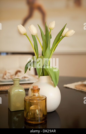 White tulips in vase on dining table - Stock Photo