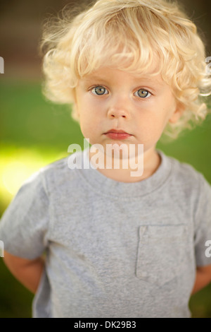 Close up portrait of innocent blonde toddler boy with curly hair in gray t-shirt - Stock Photo