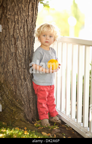 Portrait of blonde toddler boy with curly hair holding yellow ball by tree trunk and fence in backyard - Stock Photo