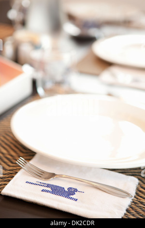 Close up of place settings and stitched Guatemalan napkin on table - Stock Photo