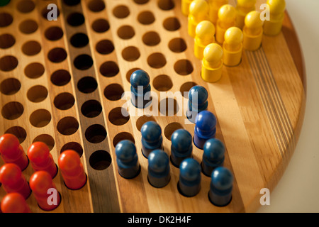 Close up high angle view of colored pegs in Chinese checkers board - Stock Photo