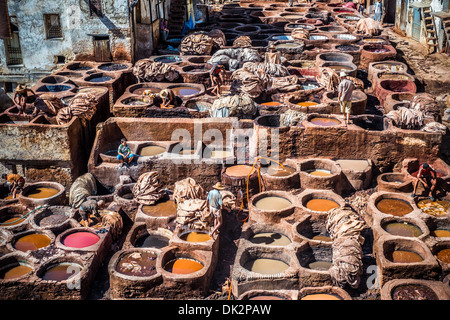 Tanners working leather in the old tannery of Fes, Morocco - Stock Photo