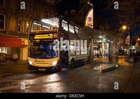 Rainy Night scene, Street lighting & Public Transport in the City of Dundee.  National Express Bus terminus in rain - Stock Photo