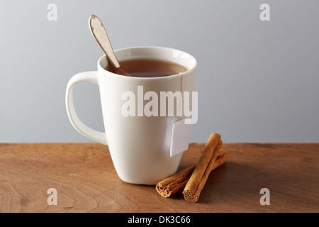 White cup of tea on wooden table with cinnamon sticks - Stock Photo