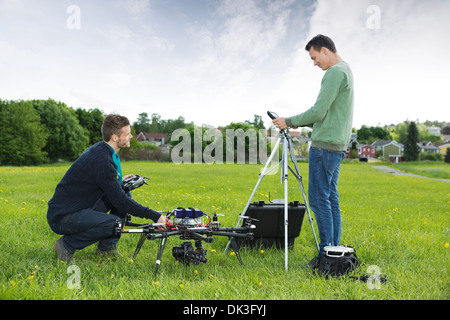 Engineers Working On UAV Helicopter in Park - Stock Photo