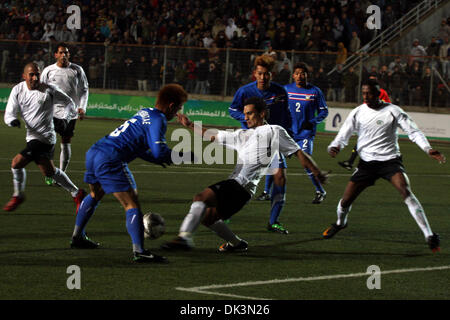 Mar 09, 2011 - Ramallah, West Bank - Palestinian (white) and Thailand  national football players fight for the ball - Stock Photo