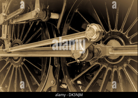 Steam train wheels with attached piston and connecting rods. A vintage sepia effect. - Stock Photo