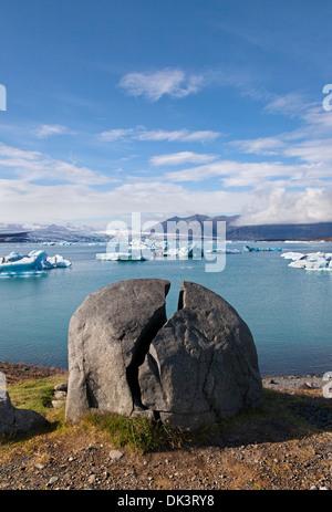 Split Rock and the Jokulsarlon Glacial Lagoon on the Border of the Vatnajokull National Park Iceland - Stock Photo