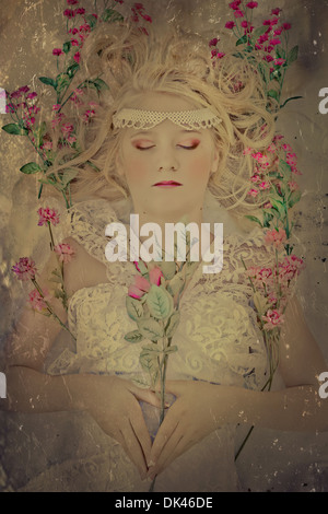 Beautiful blond woman in white lace dress asleep with flowers strewn around her - Stock Photo