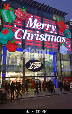 Boots chemist and pharmacy store in Oxford Street decorated and lit up with big Merry Christmas sign - Stock Photo
