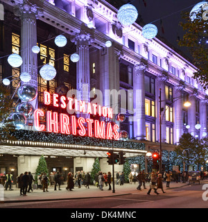 Shoppers and Christmas illuminations & decorations at Selfridges Department store main entrance Oxford Street West - Stock Photo